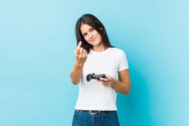 近づいてくるようにあなたに指で指しているゲームコントローラーを保持している若い白人女性。