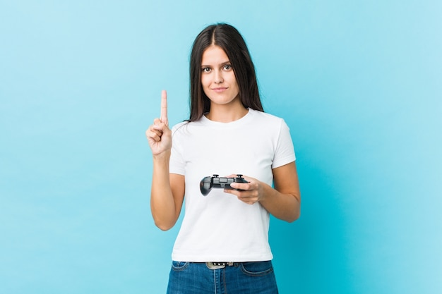 Молодая кавказская женщина, держащая игровой контроллер, показывая номер один пальцем.