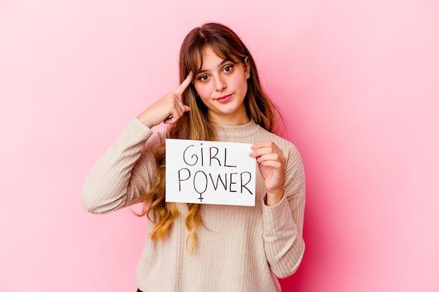 ピンクの背景に分離された女の子のパワープラカードを持っている若い白人女性は、指で寺院を指して、考えて、タスクに焦点を当てています。