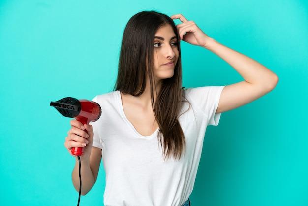疑問と混乱した表情で青い背景に分離されたヘアドライヤーを保持している若い白人女性