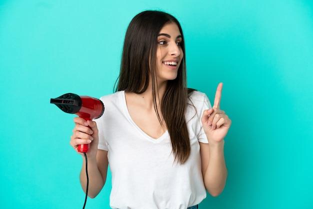 指を持ち上げながら解決策を実現することを意図して青い背景に分離されたヘアドライヤーを保持している若い白人女性