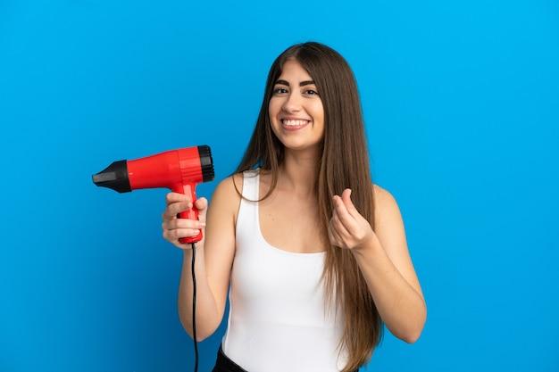 お金のジェスチャーを作る青い背景で隔離のヘアドライヤーを保持している若い白人女性