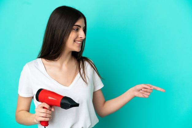 製品を提示する側を指している青い背景に分離されたヘアドライヤーを保持している若い白人女性