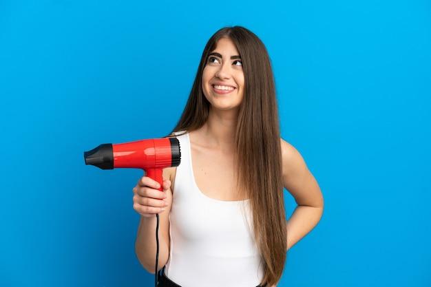 Молодая кавказская женщина, держащая фен, изолированная на синем фоне, думает об идее, глядя вверх