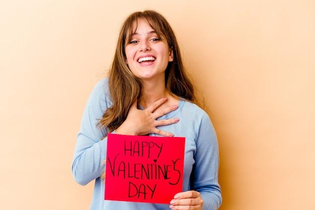 Молодая кавказская женщина, держащая счастливый день святого валентина, громко смеется, держа руку на груди.
