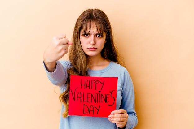 拳、攻撃的な表情を示す孤立した幸せなバレンタインデーを保持している若い白人女性。