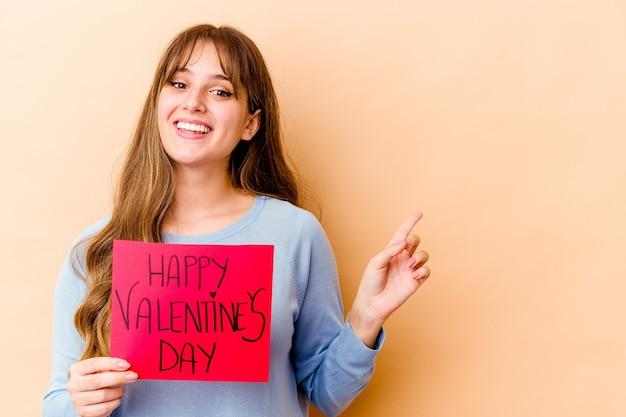 행복 한 발렌타인 데이 웃 고 옆으로 가리키는, 빈 공간에서 뭔가 보여주는 젊은 백인 여자.