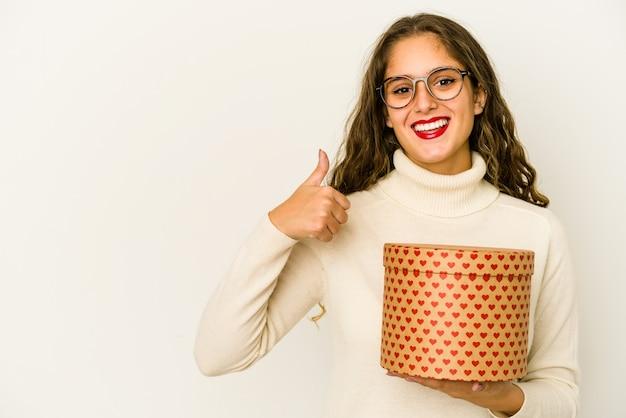 ハートバレンタインデーボックスを保持している若い白人女性は、笑顔と親指を上げて孤立