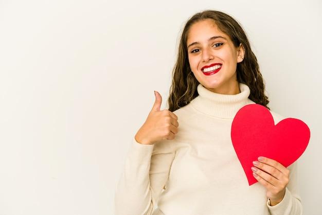 ハートのバレンタインの日の形を保持している若い白人女性は笑顔と親指を上げて孤立
