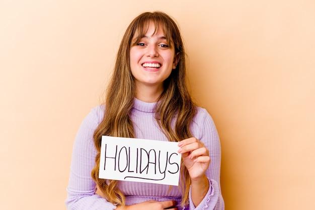 休日のプラカードを持っている若い白人女性は、笑って楽しんで孤立しました。