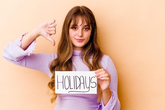 休日のプラカードを持って孤立した若い白人女性は、嫌いなジェスチャーを示して、親指を下に向けます。不一致の概念。