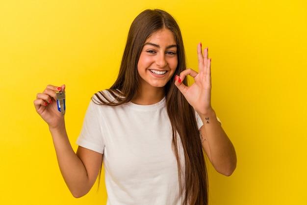 Молодая кавказская женщина, держащая ключи от дома, изолированные на желтом фоне, веселая и уверенная, показывая одобренный жест.