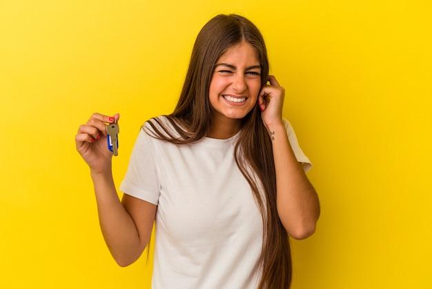 Молодая кавказская женщина, держащая ключи от дома, изолированные на желтом фоне, закрывая уши руками.