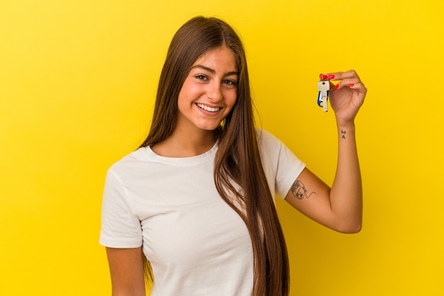 Молодая кавказская женщина, держащая ключи от дома, изолированные на желтом фоне, счастливая, улыбающаяся и веселая.