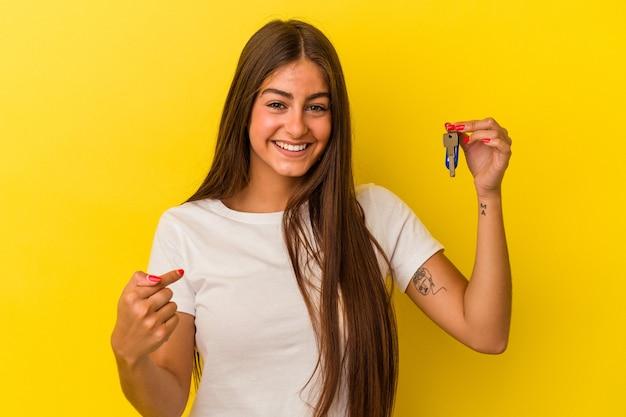 Молодая кавказская женщина, держащая ключи от дома, изолированные на желтом фоне, человек, указывая рукой на пространство для копирования рубашки, гордый и уверенный