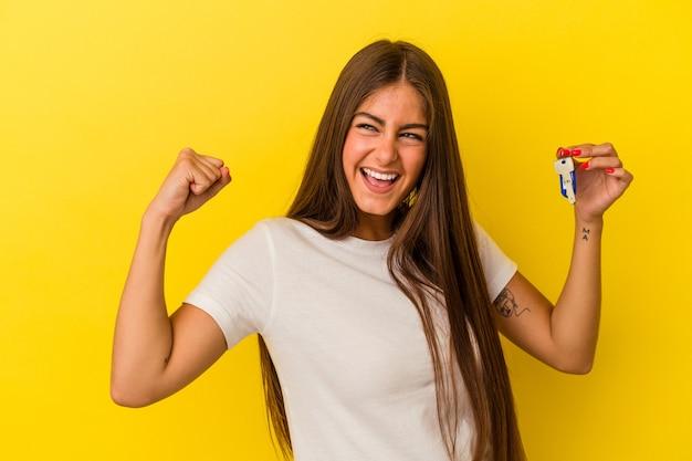 Молодая кавказская женщина держит ключи от дома, изолированные на желтом фоне, поднимая кулак после победы, концепции победителя.