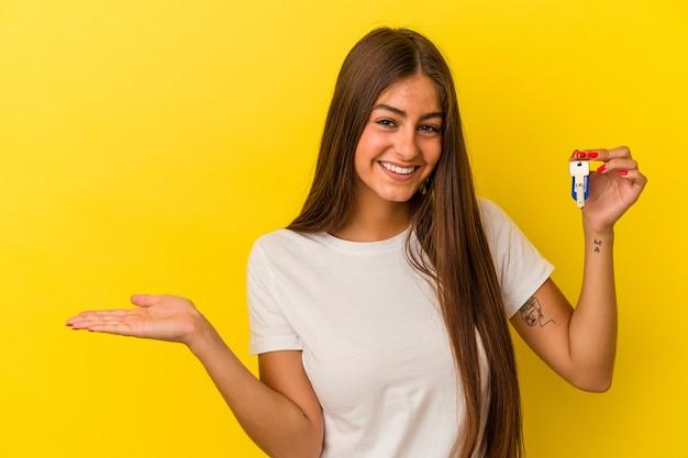 Молодая кавказская женщина, держащая ключи от дома, изолированные на желтом фоне, показывает пространство для копии на ладони и держит другую руку на талии.