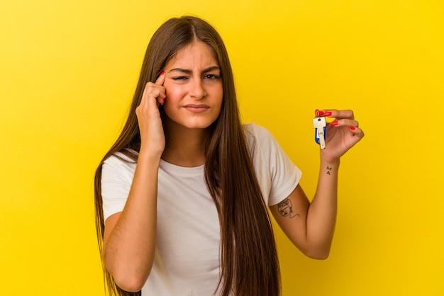 Молодая кавказская женщина, держащая ключи от дома, изолированные на желтом фоне, показывая жест разочарования указательным пальцем.