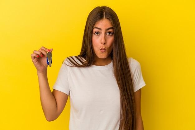 Молодая кавказская женщина, держащая ключи от дома, изолированные на желтом фоне, пожимает плечами и смущает открытые глаза.