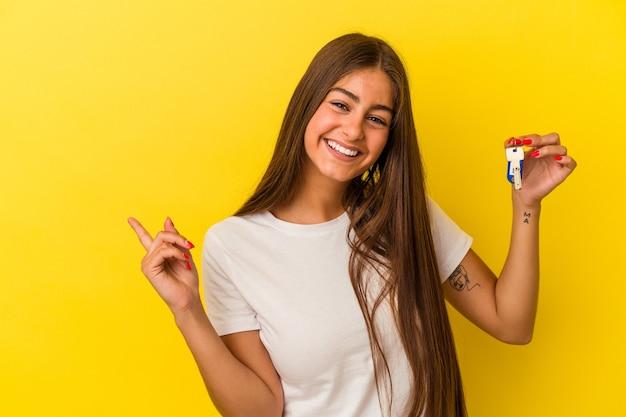 Молодая кавказская женщина держит ключи от дома, изолированные на желтом фоне, улыбаясь и указывая в сторону, показывая что-то на пустом месте.
