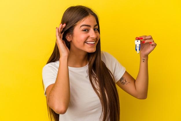 Молодая кавказская женщина, держащая ключи от дома, изолированные на желтом фоне, пытается слушать сплетни.