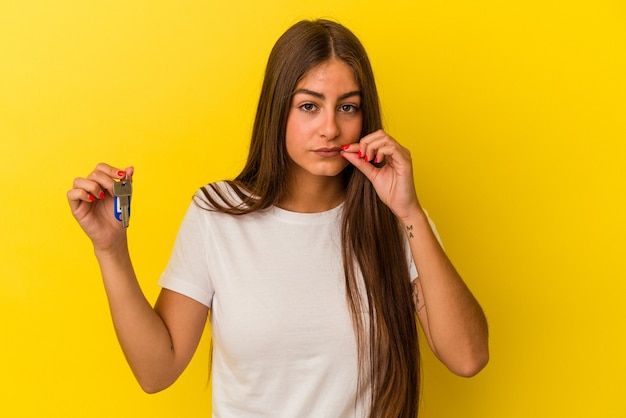 Молодая кавказская женщина держит ключи от дома, изолированные на желтом фоне с пальцами на губах, храня в секрете.