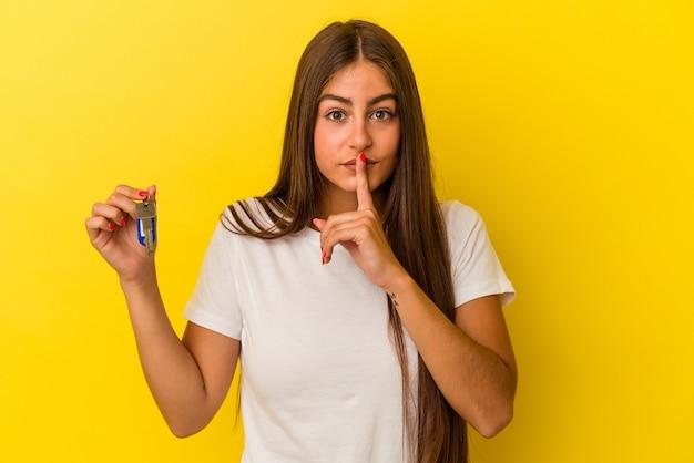 Молодая кавказская женщина, держащая ключи от дома, изолированная на желтой стене, хранит секрет или просит молчания.