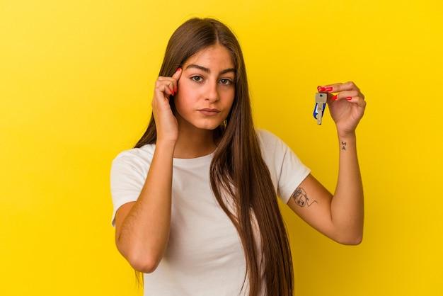 Молодая кавказская женщина, держащая ключи от дома, изолирована на желтой стене, указывая висок пальцем, думая, сосредоточилась на задаче.