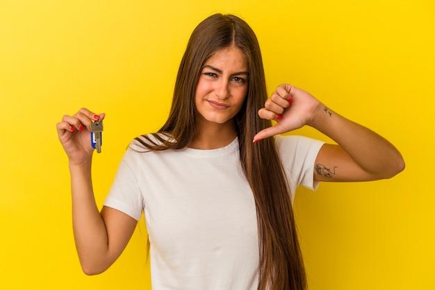 Молодая кавказская женщина, держащая ключи от дома, изолированные на желтой стене, показывает жест неприязни, пальцы вниз. концепция несогласия.