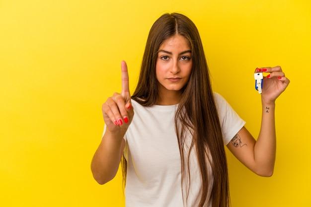 Молодая кавказская женщина, держащая ключи от дома, изолированные на желтой стене, показывая номер один пальцем.