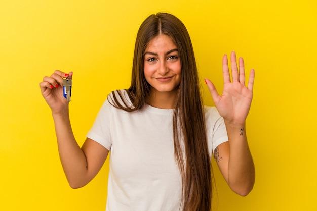 Молодая кавказская женщина, держащая ключи от дома, изолированная на желтой стене, улыбается веселый, показывая номер пять с пальцами.