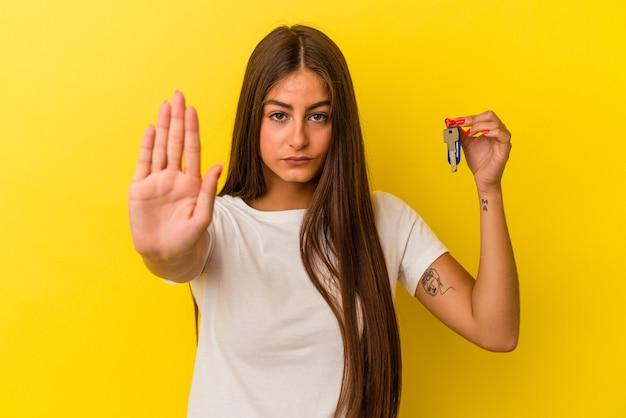Молодая кавказская женщина, держащая ключи от дома, изолирована на желтой стене, стоящей с протянутой рукой, показывая знак остановки, предотвращая вас.