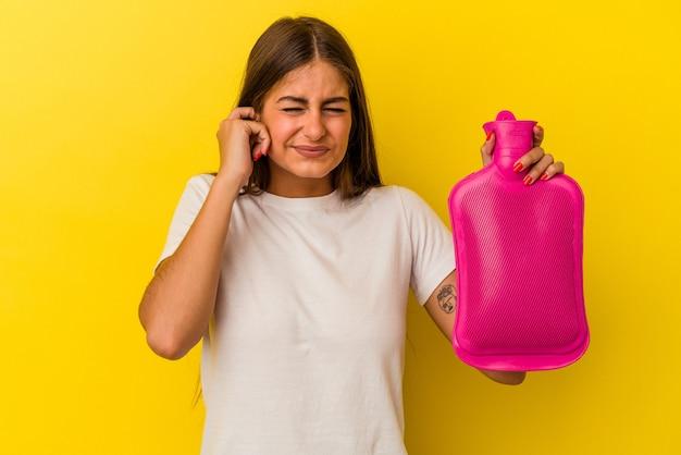 手で耳を覆う黄色の背景に分離された湯たんぽ水を保持している若い白人女性。