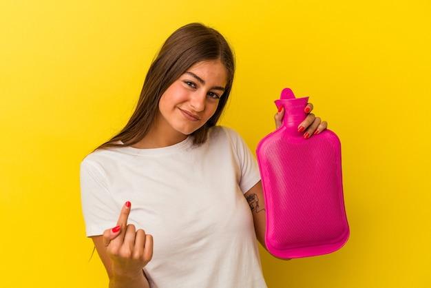 黄色の背景に分離された湯たんぽの水を持っている若い白人女性が、誘うようにあなたに指を向けて近づいています。