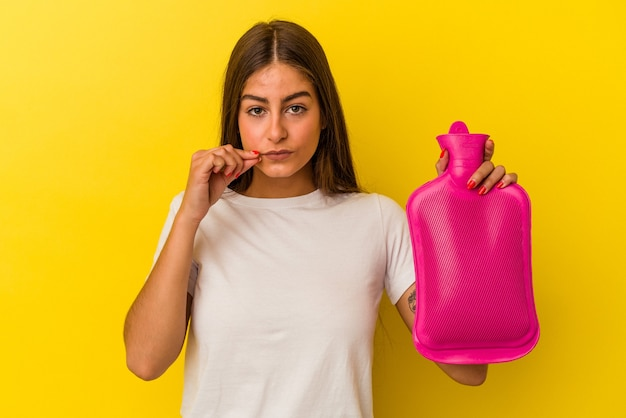 秘密を保持している唇に指で黄色の背景に分離された湯たんぽ水を保持している若い白人女性。