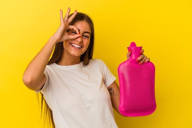 黄色い壁に隔離された湯たんぽの水を持っている若い白人女性は、目の上で大丈夫なジェスチャーを維持して興奮しました。
