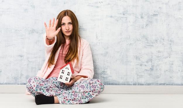 一時停止の標識を示す伸ばした手で立っている家のアイコンを保持している若い白人女性は、あなたを防ぎます。