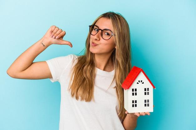 青の背景に家のモデルを持っている若い白人女性は、誇りと自信を持って、従うべき例を示しています。
