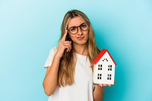 指で寺院を指し、思考、タスクに焦点を当て、青い背景で隔離の家のモデルを保持している若い白人女性。