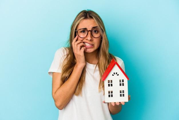 손톱을 물고 파란색 벽에 고립 된 집 모델을 들고 젊은 백인 여자, 긴장과 매우 불안