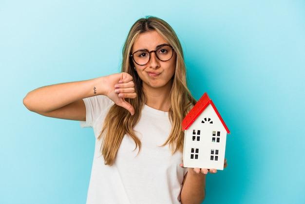 싫어하는 제스처를 보여주는 파란색 벽에 고립 된 집 모델을 들고 젊은 백인 여자, 아래로 엄지