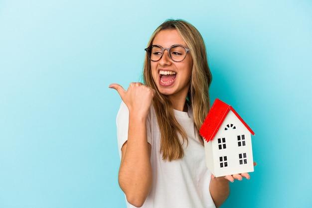 집 모델을 들고 젊은 백인 여자는 엄지 손가락으로 멀리, 웃음과 평온한 가리 킵니다.