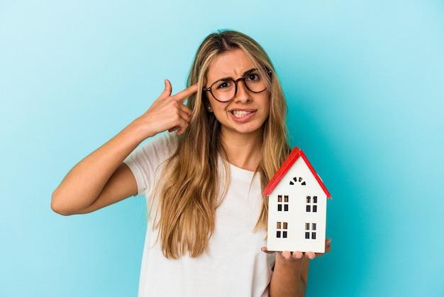 집게 손가락으로 실망 제스처를 보여주는 집 모델을 들고 젊은 백인 여자.