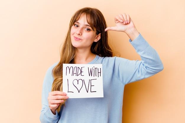 孤立した愛のプラカードで作られた若い白人女性は、誇りと自信を持って、従うべき例を感じます。
