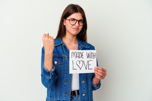 指で寺院を指して、白い背景に分離された愛のプラカードで作られた若い白人女性は、タスクに焦点を当てて考えています。