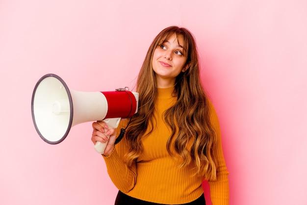 Молодая кавказская женщина, держащая мегафон изолирована, мечтает о достижении целей и задач
