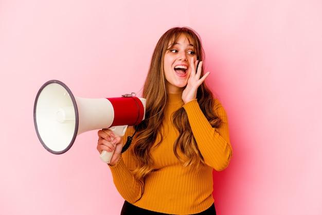 Молодая кавказская женщина, держащая мегафон, кричит и держит ладонь возле открытого рта.