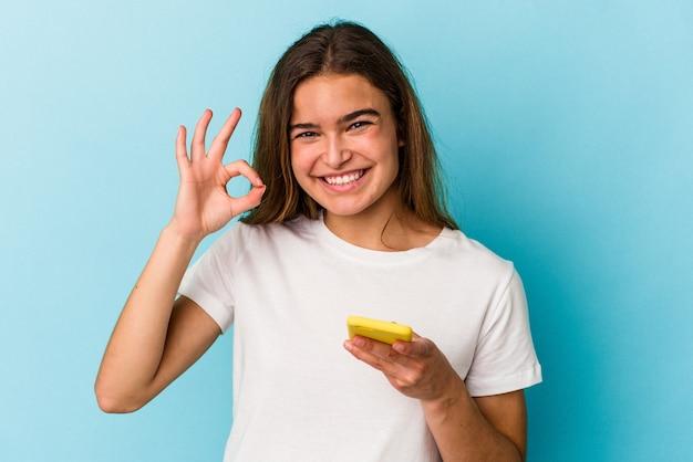 Молодая кавказская женщина, держащая мобильный телефон, изолированная на синем фоне, веселая и уверенная, показывая одобренный жест.
