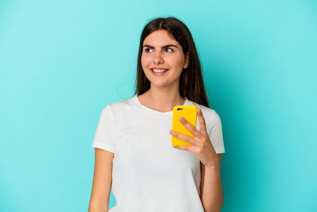 목표와 목적을 달성하는 꿈을 파란색 배경에 고립 된 휴대 전화를 들고 젊은 백인 여자