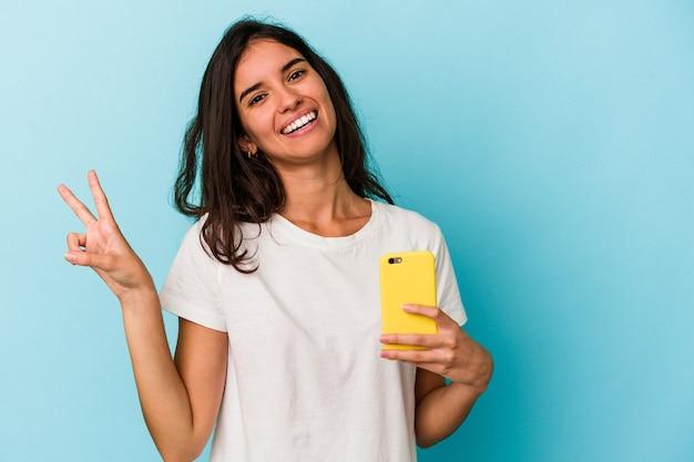 青い背景に分離された携帯電話を持っている若い白人女性は、指で平和のシンボルを示して楽しくてのんきです。